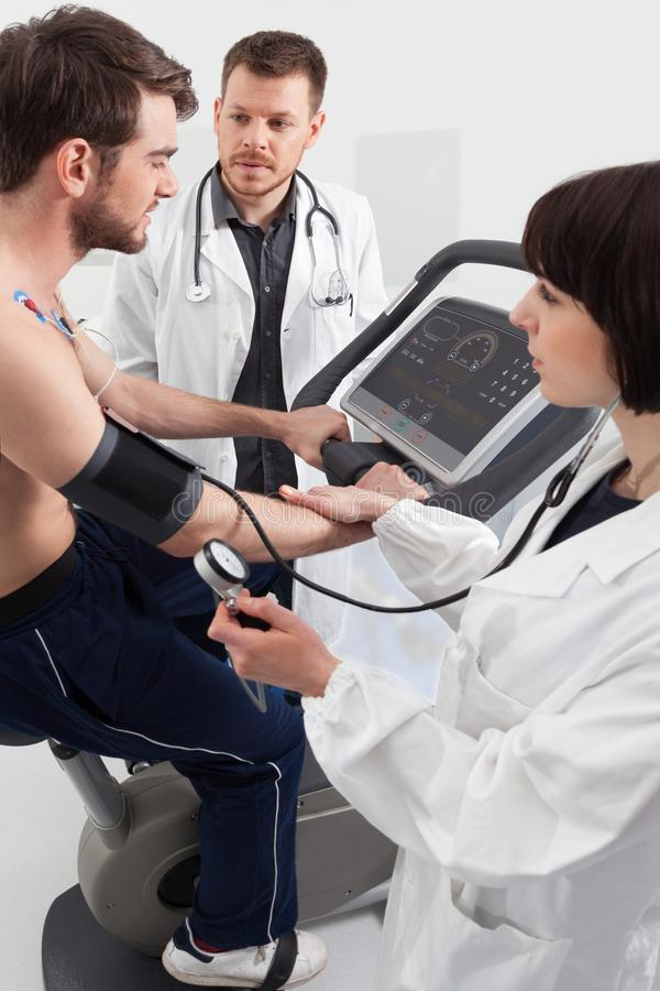 Doctor and nurse examination of cardiac stress test. A male patient, pedaling on a bicycle ergometer stress test for the function of his heart checked royalty free stock photography