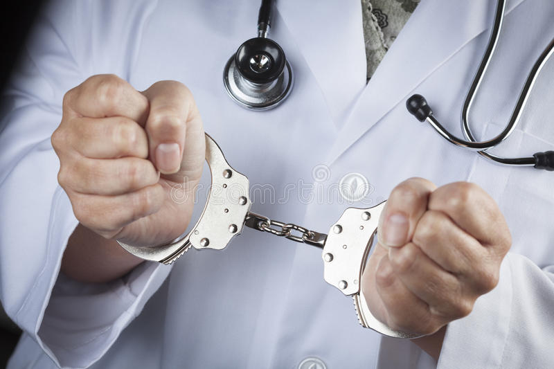 Doctor or Nurse In Handcuffs Wearing Lab Coat and Stethoscope stock photos