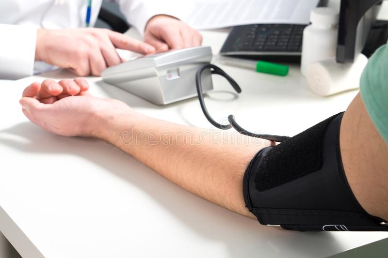 Doctor or nurse measure blood pressure of a patient. Doctor or nurse measure blood pressure of a patient with meter and monitor device. Hand and arm on stock photo