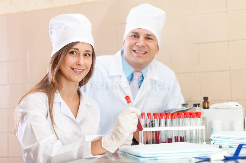 Doctor and nurse in medical laboratory. Male doctor and nurse with test tubes makes blood test in medical laboratory royalty free stock image