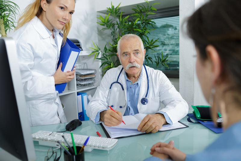 Doctor and nurse with patient. Doctor and nurse with a patient stock image