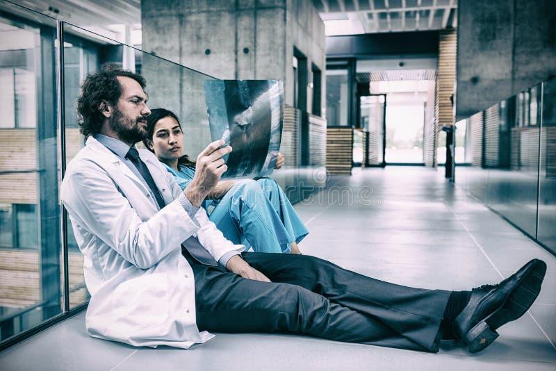 Doctor and nurse sitting on floor examining X-ray report. Stressed doctor and nurse examining X-ray report in hospital corridor stock photo