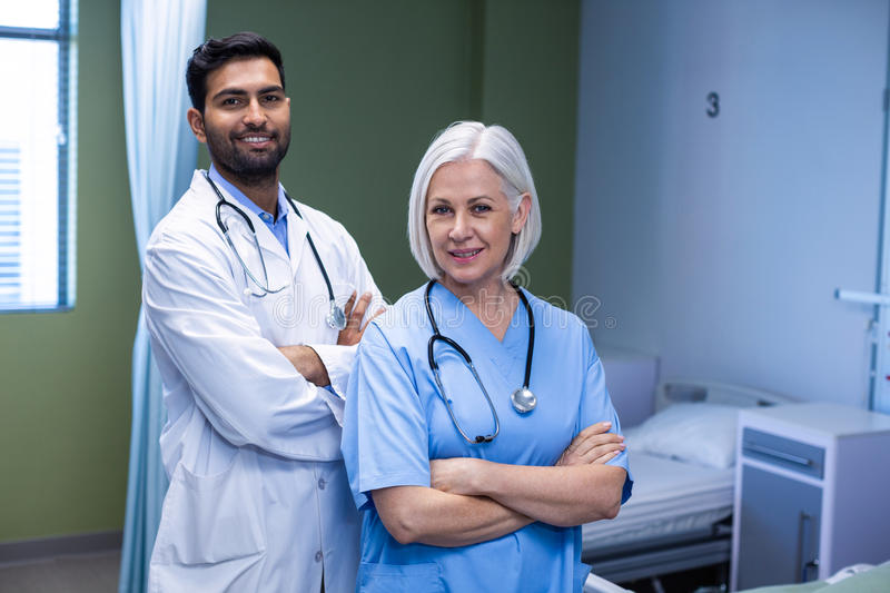 Doctor and nurse standing with arms crossed in hospital stock images