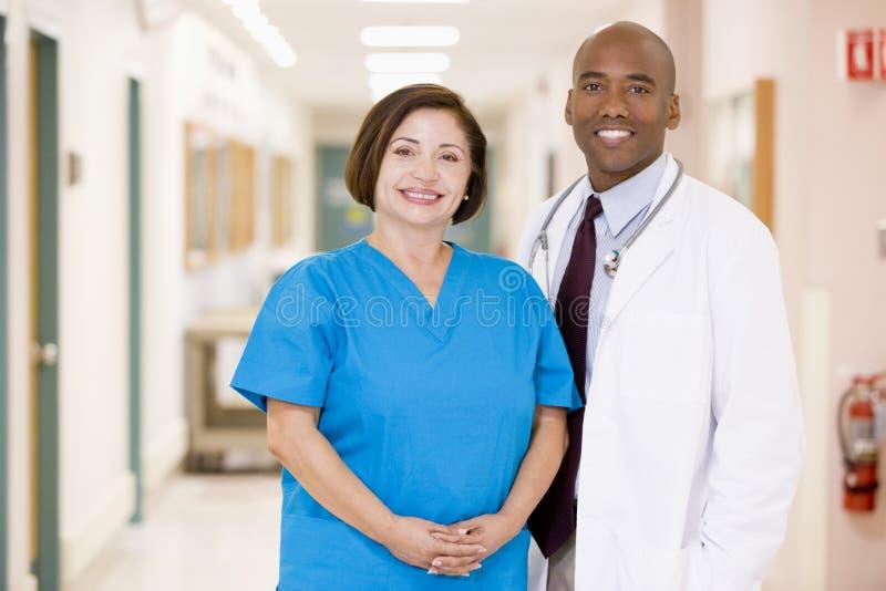 A Doctor And Nurse Standing In A Hospital Corridor stock photos