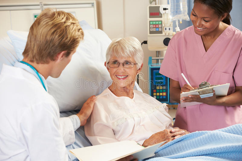 Download Doctor With Nurse Talking To Senior Female Patient In Bed Stock Photo - Image: 28705290