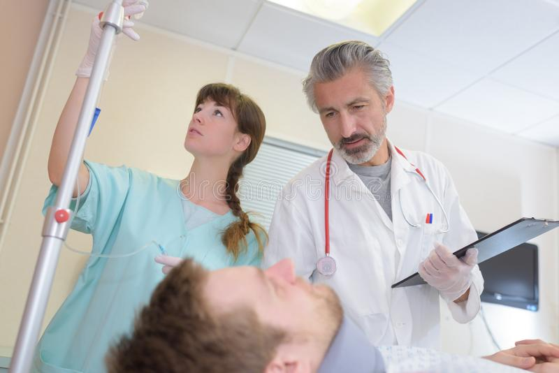 Doctor and nurse tending to patient wearing neck brace. Doctor stock image