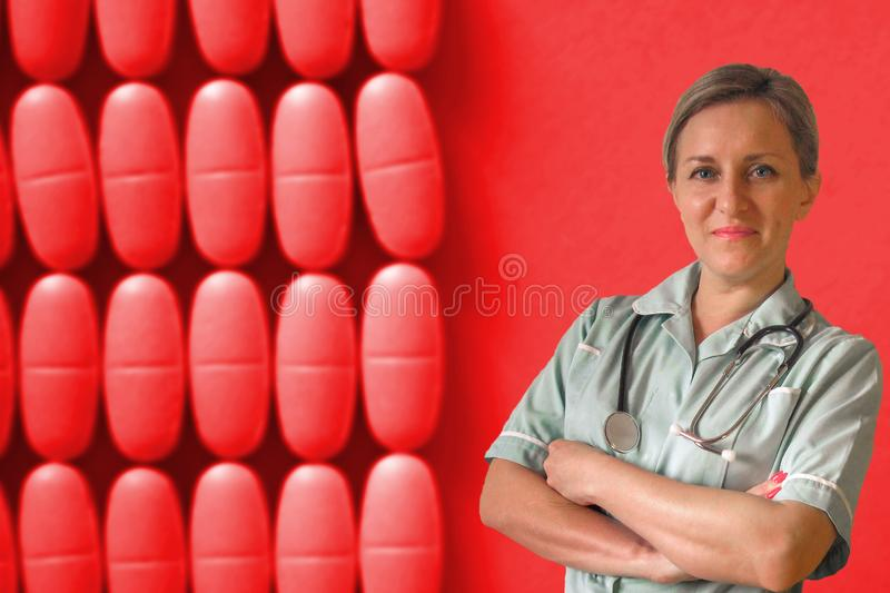 Doctor or nurse in uniform with stethoscope around neck and crossed hands. Happy positive smiled white woman. On red drug royalty free stock photography