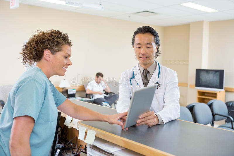 Doctor And Nurse Using Digital Tablet At Hospital. Mature doctor and nurse using digital tablet at hospital reception stock photos