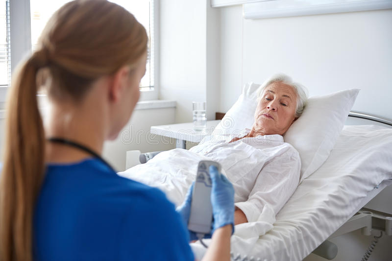 Doctor or nurse visiting senior woman at hospital. Medicine, age, support, health care and people concept - doctor or nurse adjusting bed with remote control for stock photos