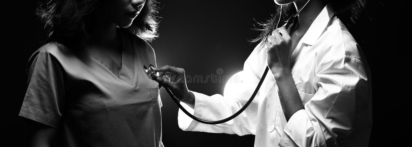 Doctor Nurse woman in uniform with stethoscope check heart rate. Asian Beautiful Doctor Nurse women in uniform with stethoscope check heart rate of patient royalty free stock photo