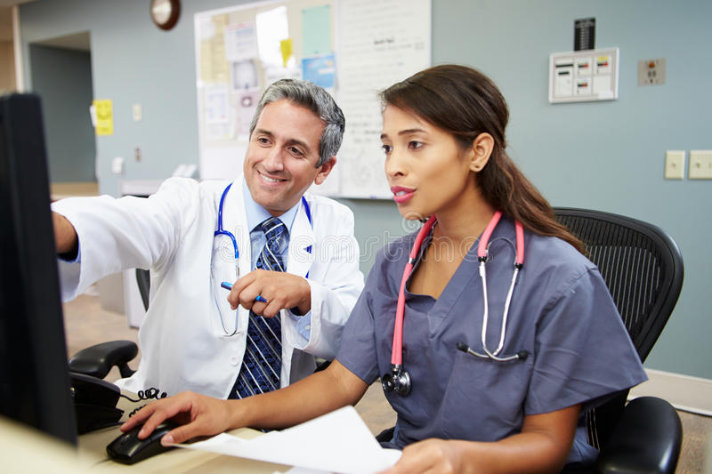Doctor With Nurse Working At Nurses Station stock photography