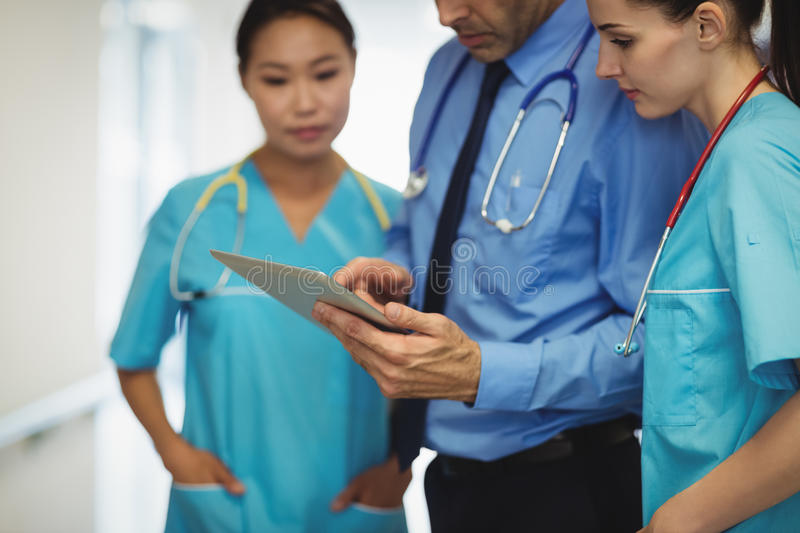Doctor and nurses discussing over digital tablet. At the hospital stock photos