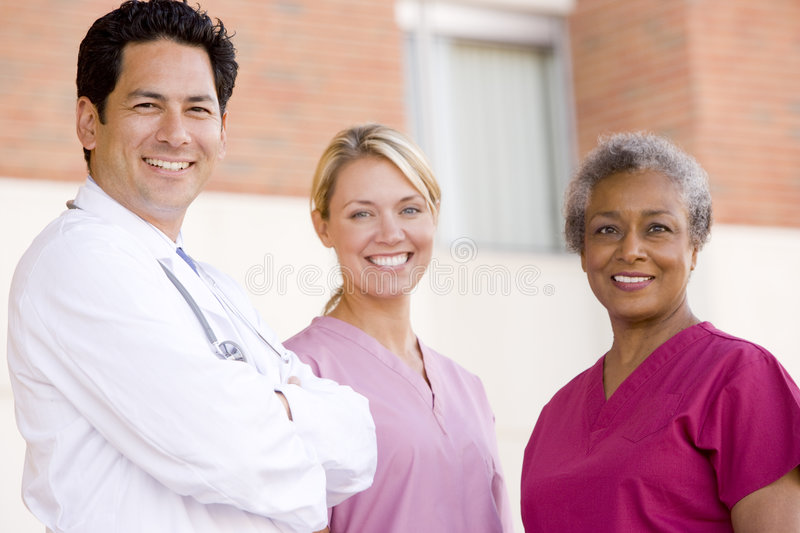 Doctor And Nurses Standing Outside A Hospital. Smiling royalty free stock images