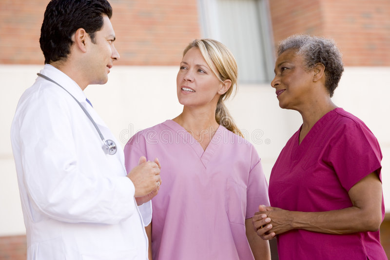 Doctor And Nurses Standing Outside A Hospital. Smiling royalty free stock image