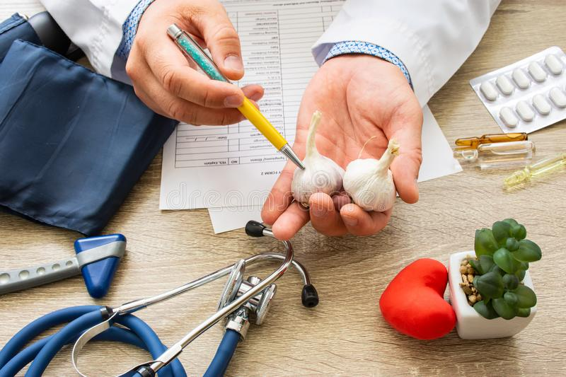 Doctor nutritionist during consultation held in his hand and shows patient garlic bulb. Counseling and explanation of use of garli stock photo