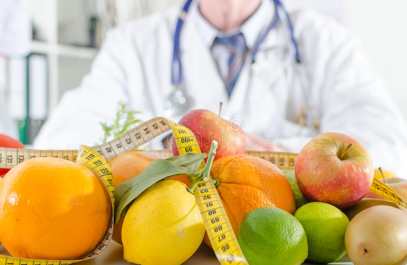 Doctor nutritionist with healthy fruits stock photography