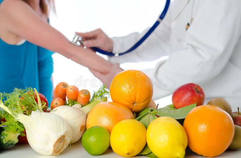 Doctor nutritionist measuring blood pressure of his patient stock image