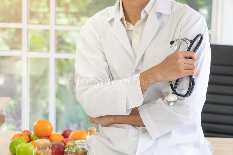Doctor or nutritionist sitting on the desk with fruit and Vitamin bottle in clinic. Healthy diet Concept of nutrition food as a royalty free stock image