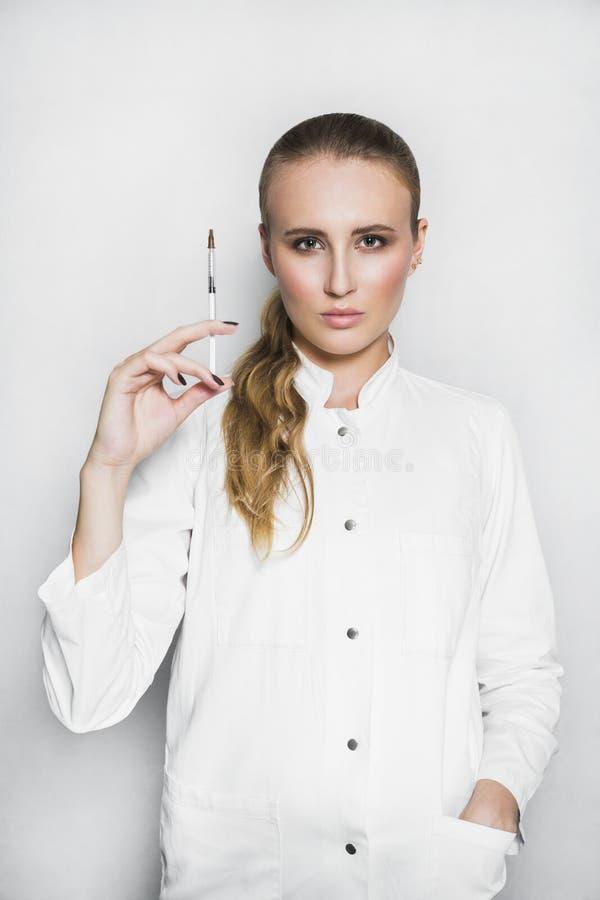 Doctor o científico de sexo femenino en vestido médico con la jeringuilla en el fondo blanco fotografía de archivo libre de regalías