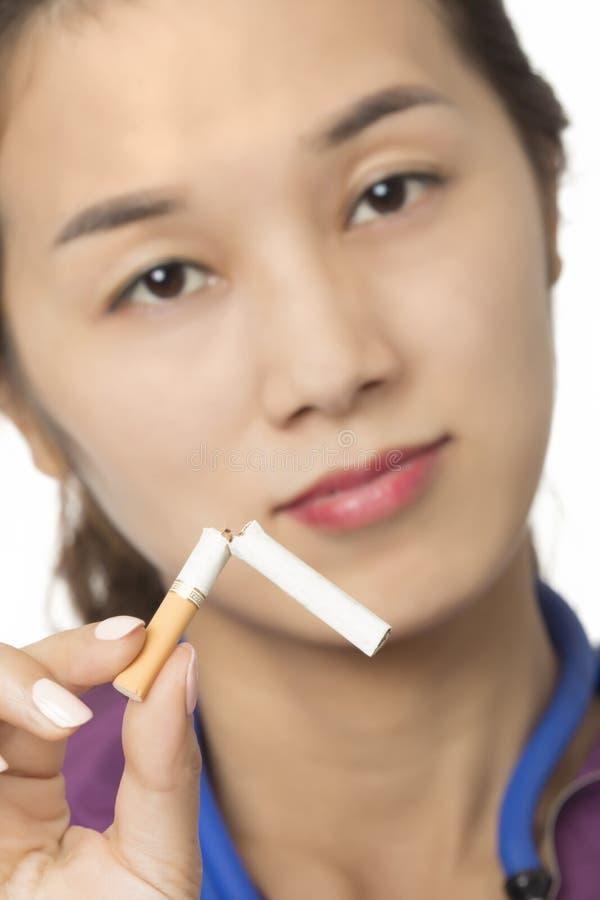 Doctor o enfermera asiático que sostiene un cigarrillo quebrado fotos de archivo