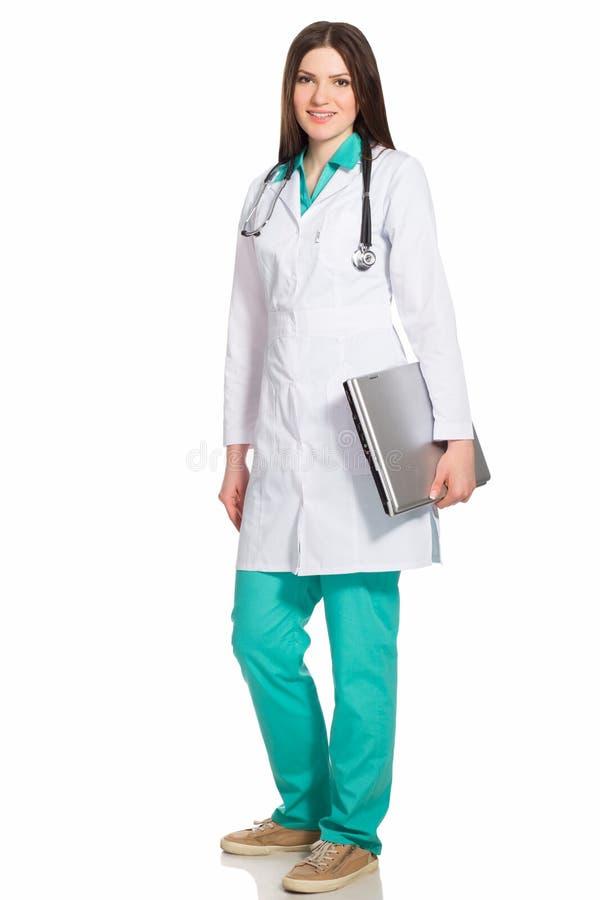 Doctor o enfermera de la mujer joven con el ordenador portátil imagenes de archivo