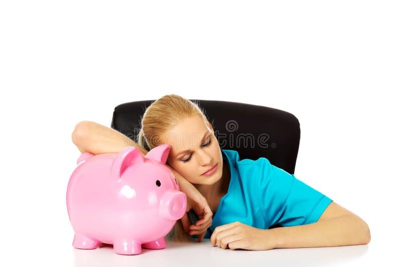 Doctor o enfermera de sexo femenino cansado joven que se sienta detrás del escritorio y que lleva a cabo un piggybank imagen de archivo libre de regalías