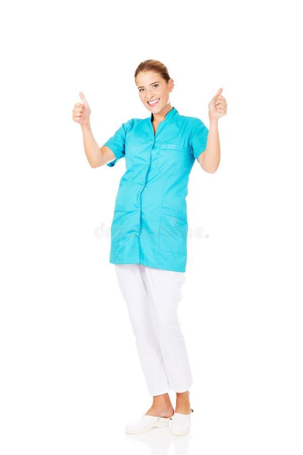 Doctor o enfermera de sexo femenino joven de la sonrisa con los pulgares para arriba imagen de archivo