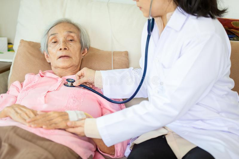Doctor o enfermera de sexo femenino médico de la familia que comprueba al paciente mayor usando el estetoscopio en la cama de hos imágenes de archivo libres de regalías
