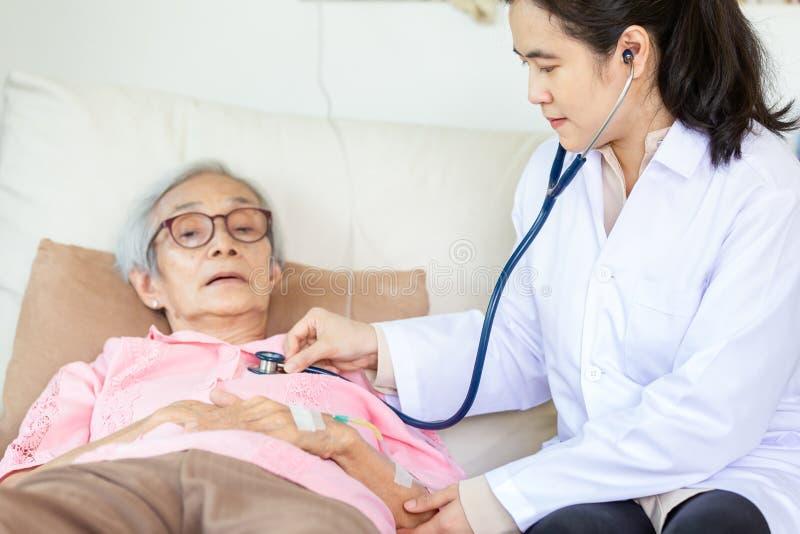 Doctor o enfermera de sexo femenino médico de la familia que comprueba al paciente mayor usando el estetoscopio en la cama de hos imagen de archivo libre de regalías