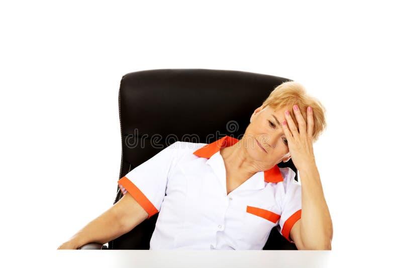 Doctor o enfermera de sexo femenino mayor que se sienta detrás del escritorio con dolor de cabeza fotos de archivo libres de regalías