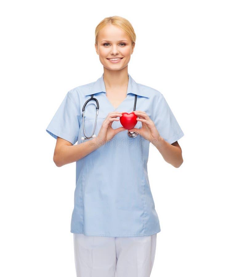 Doctor o enfermera de sexo femenino sonriente con el corazón fotos de archivo
