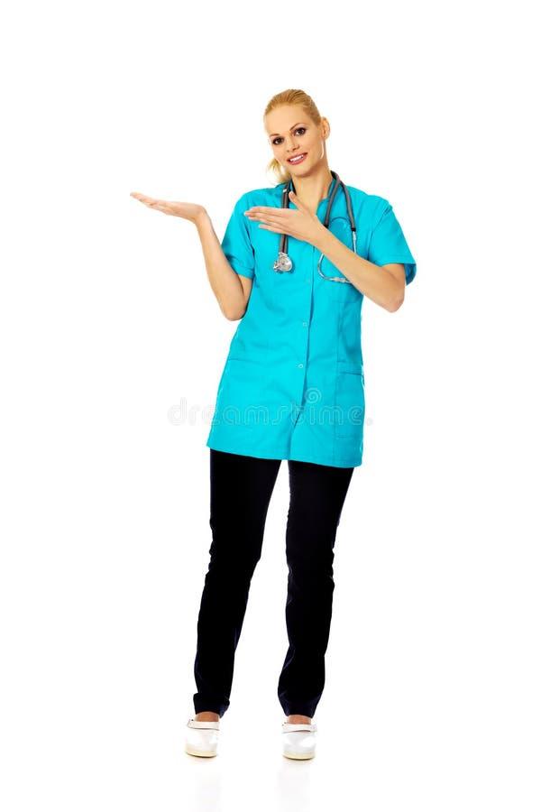 Doctor o enfermera de sexo femenino sonriente que presenta el copyspace o algo en la palma abierta y que señala para esto imagen de archivo