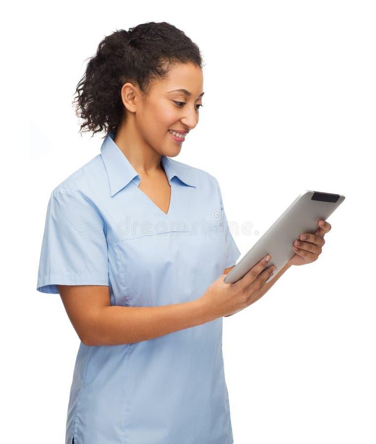Doctor o enfermera negro sonriente con PC de la tableta imagenes de archivo