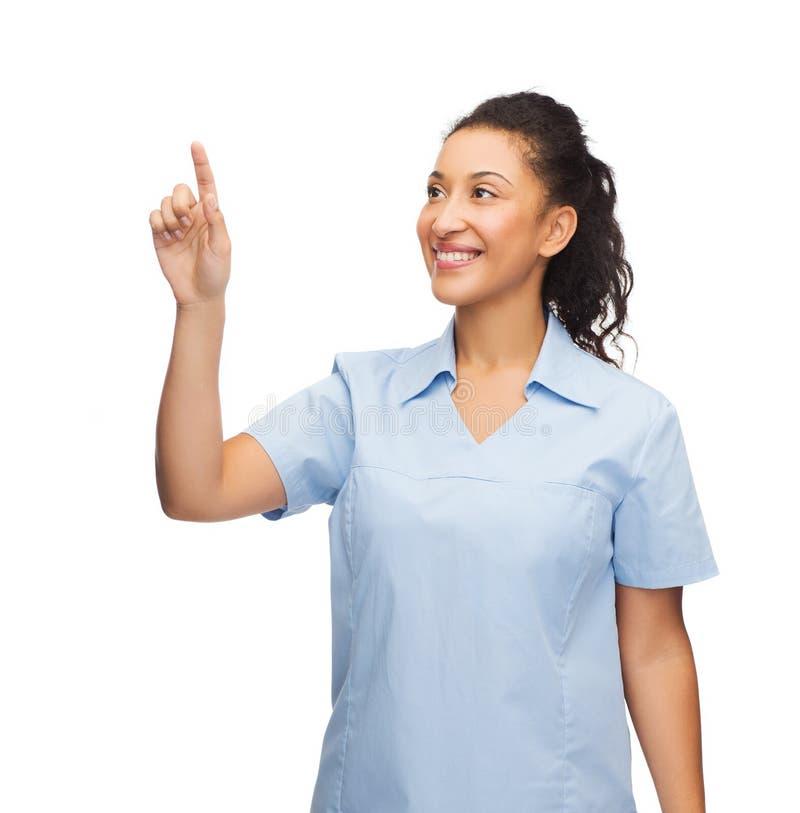 Doctor o enfermera sonriente que señala algo fotos de archivo
