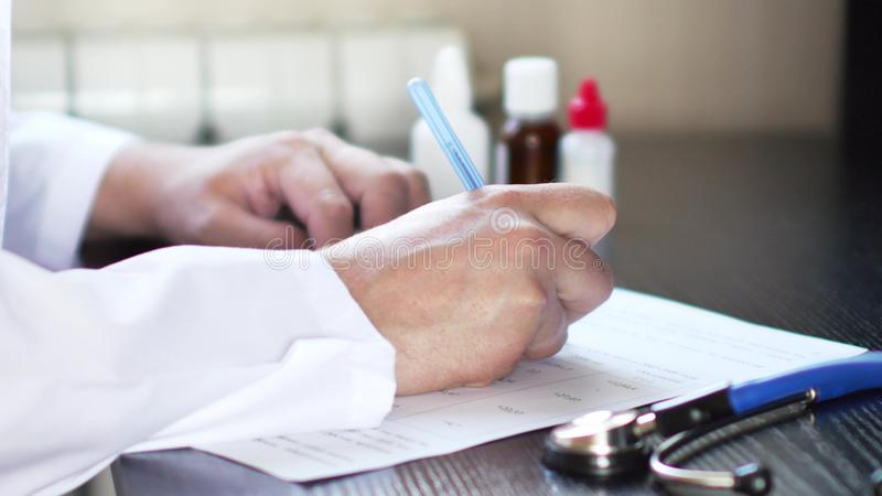 Doctor o farmacéutico que se sienta en la tabla y que escribe la prescripción en forma de RX fotografía de archivo