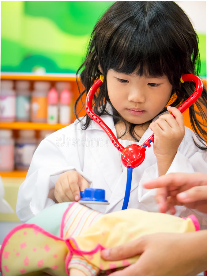 Doctor occupation role playing girl. Adorable asian girl role playing doctor occupation wearing white gown uniform stock photo