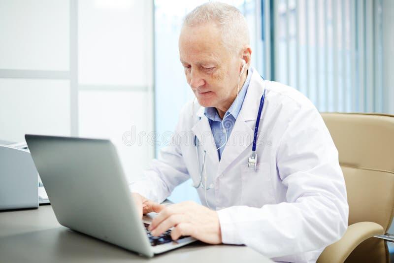 Doctor ocupado que hace informe en el ordenador portátil fotografía de archivo libre de regalías