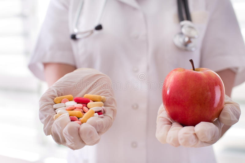 Doctor offering pills and apple to choose stock image