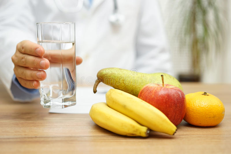 Doctor is offering water and fruit after reading diagnose. Healt. Hy life and health care concept royalty free stock photos