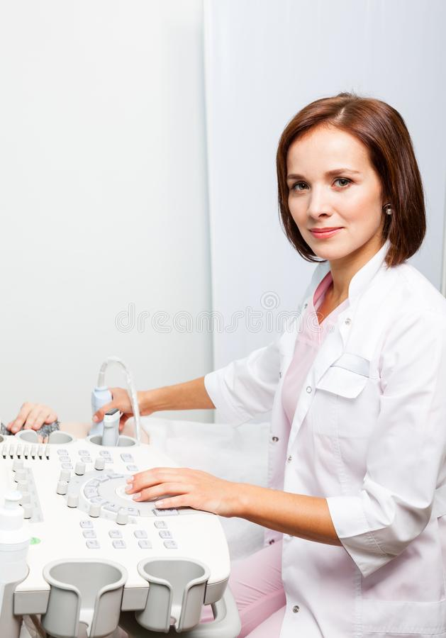 Doctor operating ultrasound machine performing obstetric ultrasonography stock photography