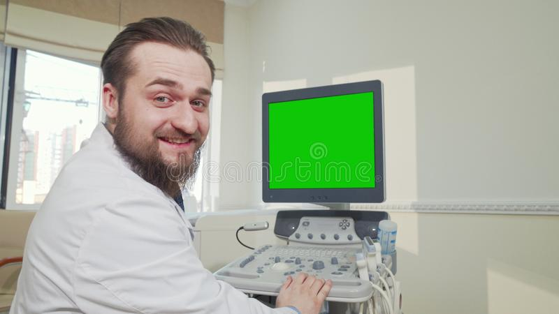 Doctor operating ultrasound scanner with green screen. Rear view shot of a male practitioner using ultrasound scanner with green mock up screen. Physician stock photos