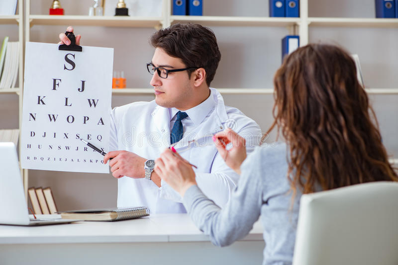 The doctor optician with letter chart conducting an eye test check stock images