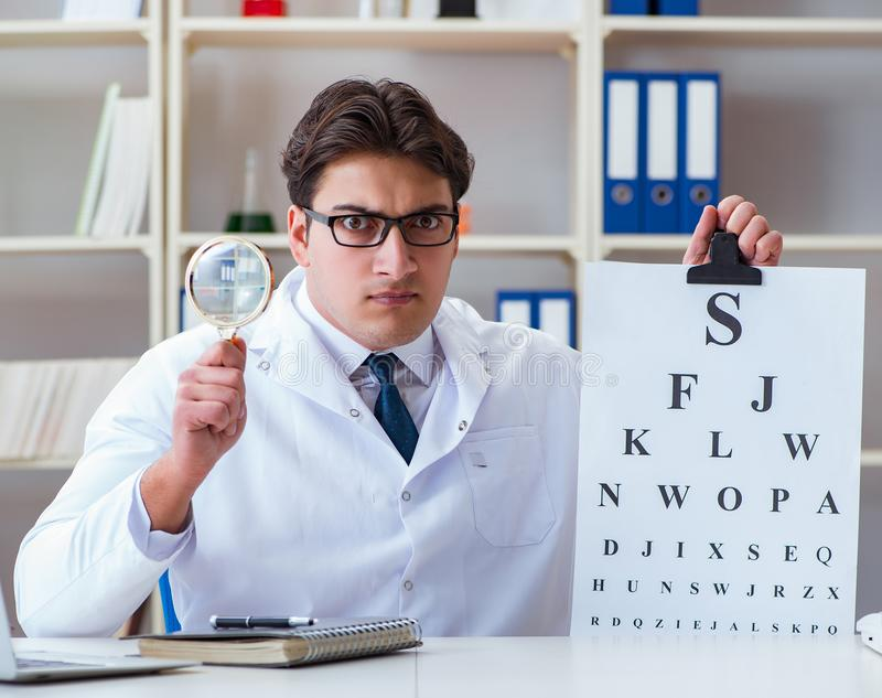 Doctor optician with letter chart conducting an eye test check. The doctor optician with letter chart conducting an eye test check royalty free stock photography