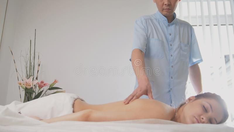 Doctor osteopat and patient - young woman lying on massage table - medical treatment stock photo