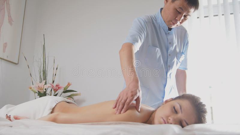 Doctor osteopat and patient - young woman lying on massage table - medical treatment stock photography