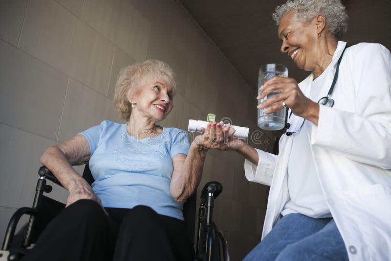 Doctor paciente inhabilitado Giving Medicines To foto de archivo