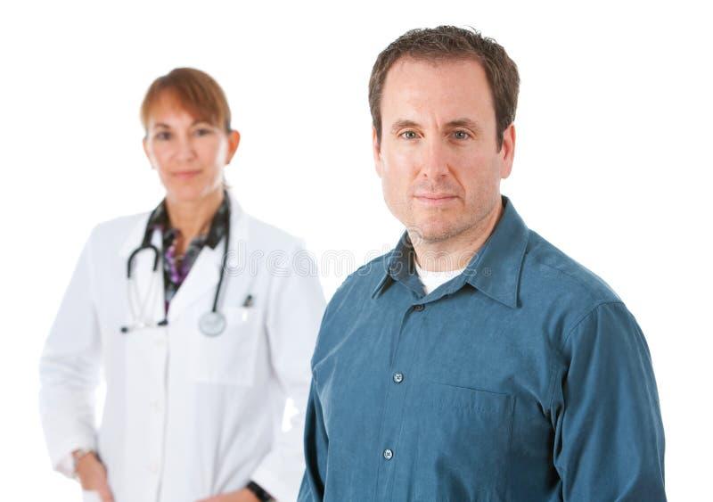 Doctor: Paciente serio con el médico Behind fotografía de archivo libre de regalías