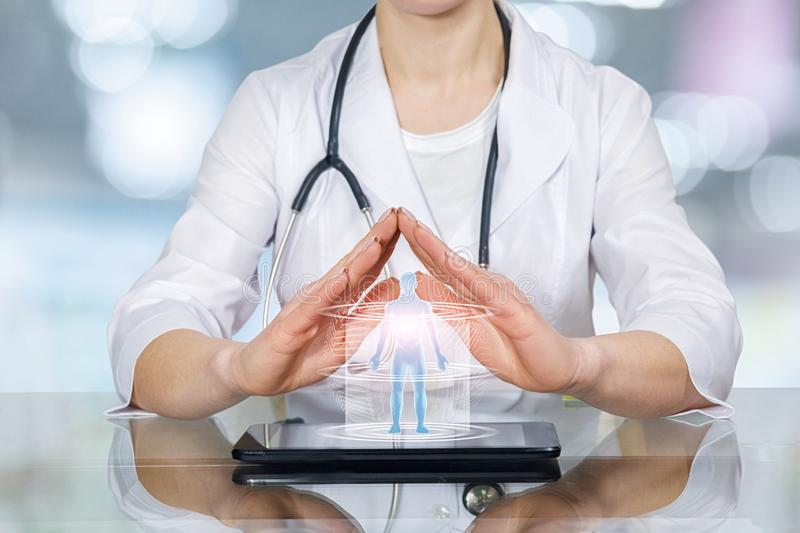 A doctor palms in protection position under the human figure model royalty free stock photo