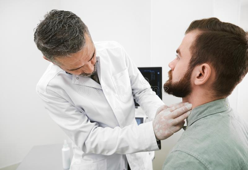Doctor in medical gloves palpating man`s neck. Doctor palpating and examining lymph nodes on man`s neck. Bearded patient sitting on examination in medical stock images
