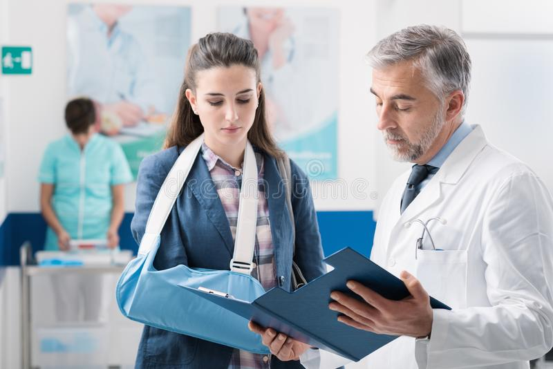 Doctor with a patient with broken arm royalty free stock photography